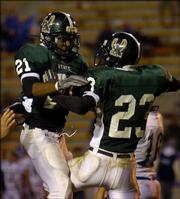 Free State High's Brian Murphy, left, and Nick Ayre celebrate Ayre's touchdown in the fourth quarter against Topeka Washburn Rural. The Firebirds beat the Junior Blues, 32-15, Friday at Haskell Stadium and advanced to the Class 6A state playoffs.