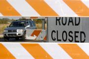 Framed through a road construction sign, a car maneuvers through construction on westbound Sixth Street.