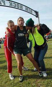 Cross country workers Kaite Renyer, left, and Megan Hrenchin help Free State High's Alysha Valencia. The Firebirds' senior collapsed at the finish line after finishing sixth Saturday at the Class 6A state championships at Rim Rock Farm.