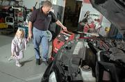Rob Wendland, owner of Wendland Performance, 2103 W. 26th St., runs a MotorVac on an SUV Saturday to help clean the fuel system and improve engine performance. Pictured along with Wendland is his daughter, Mykala, 4.