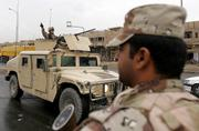 A U.S. soldier gestures from a humvee as he patrols a street Saturday in Baghdad, Iraq. The campaign for Iraq's parliamentary election effectively began Saturday for the 18 candidates.