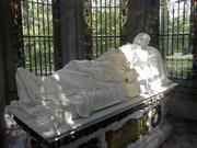 A marble statue of Henry Shaw rests above his tomb in the mausoleum outside Tower Grove House. He clasps a single rose in his right hand.