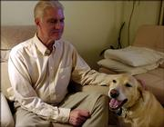 Popular Science magazine recently ranked Kansas biology teacher as one of the worst jobs in science. Lawrence High School teacher Bob Hubert thinks that the rankings are a big exaggeration. Hubert is pictured at his home Monday with his dog Shea.