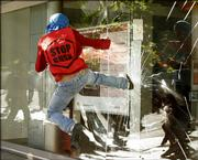A protester kicks in a window of a bank Friday during a march against the presence of President Bush in the Fourth Summit of the Americas in the Atlantic resort city of Mar del Plata, Argentina.