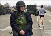 An unidentified U.S. Army member jogs as a Romanian anti-terrorist squad soldier looks on in at the Mihail Kogalniceanu air base. Human Rights Watch in New York said Thursday it had evidence indicating the CIA transported suspected terrorists captured in Afghanistan to Poland and Romania.