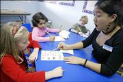 Christine Kim, right, helps Jillian Sommerauer, left, with the proper pronunciation of a word during a reading lesson as Neha Gulrajani, center, and Jacob Hall work on math problems at the Kumon Math and Reading Center Thursday in Overland Park. The children are part of a trend that has led to an increase in preschool learning centers and controversy over the value of such programs.