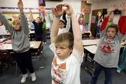 Fifth-graders, including, from front left, Emily Jacobs, Dalton Meyer and Jacob Richardson, participate in a morning stretch recently in Cindy Merten's class at Challenger Intermediate School in Goddard.