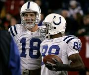 Indianapolis quarterback Peyton Manning, left, congratulates wide receiver Marvin Harrison after his fourth-quarter touchdown catch against New England. The Colts won, 40-21, Monday in Foxborough, Mass.