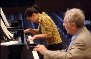 Yale School of Music masters student Xinyu Chen, left, performs Thursday during class under the instruction of professor Claude Frank in New Haven, Conn. After receiving a $100 million donation, the School of Music will fully subsidize students' tuition beginning next year.