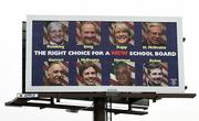 A billboard with the opponents to the current Dover Area School Board is seen Tuesday above Main Street in Dover, Pa. Voters swept out the conservative members of the board.