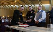 Maj. Jeff Daniels cuts a slice of cake for Marines Lance Cpl. Ryan Chapman, 23, Lawrence, center, and Charley Henson, 88, retired, Lawrence, during a ceremony Thursday morning celebrating the 230th birthday of the U.S. Marine Corps at the Dole Institute of Politics.
