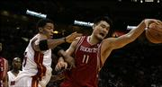 Miami forward Wayne Simien, left, tries to gain control of the ball as Houston center Yao Ming stretches for the rebound. The Heat won, 88-84, Thursday in Miami.