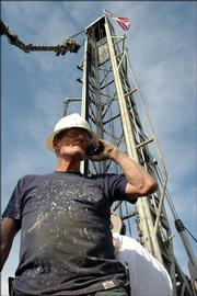 Mike Glaze, who's been drilling oil wells for decades, takes a phone call in front a new well just west of Gardner. With oil fetching nearly $60 a barrel, drilling has once again become big business in the state, though drillers are cautiously optimistic.