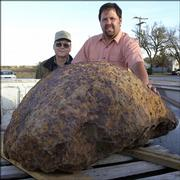 Allen Binford, left, poses with Steve Arnold, and the 1,400-pound meteorite that was discovered on Binford's farm. Arnold, a professional meteorite hunter from Kingson, Ark., found the rock underground two weeks ago in Kiowa County's Brenham Township.