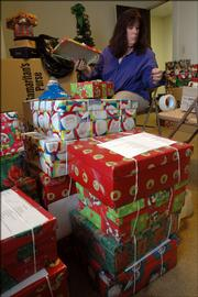 Members of First Christian Church are putting together Christmas gift packages for children around the world through the national program Operation Christmas Child. Elaine Horton wrapped gift boxes Wednesday at the church, 1000 Ky.