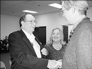 Richard Fraser, left, receives congratulations from John Naughton, grand master with District 12, for serving 25 years as a Mason by Lawrence Lodge No. 6. Fraser's wife, Shirley, looks on. He was recognized during a ceremony Oct. 10.