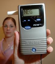 Once the school district's new anti-drinking policy takes effect, all students will be tested for alcohol before dances. Andrea Diggs, administrative assistant with the school district's Safe School/Healthy Student department, holds the breath alcohol tester that will be used to screen students.