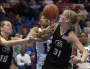 Emporia State's Andi McAlexander (10) and Michelle Steuve (31) battle Kansas University's Taylor McIntosh for a rebound. The Jayhawks beat ESU, 83-53, in an exhibition Sunday in Allen Fieldhouse.