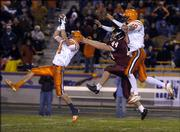 Olathe East's Adam Parks, left, intercepts a pass intended for Lawrence High's Scott Penny (44) as O-East's Derek Miller defends. The pickoff came late in the Lions' 22-18 Class 6A state semifinal loss on Friday at Haskell Stadium.