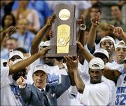 North Carolina coach Roy Williams holds the trophy with his team after the Tar Heels beat Illinois, 75-70, in the NCAA championship game. Williams, shown April 4 in St. Louis, and the now-unranked Tar Heels lost four underclassmen to the NBA and their top seven scorers from last season, leaving behind a short bench and a freshman-heavy rotation.