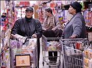 Carolyn Ewing, left, and other shoppers make their grocery selections at a Chicago supermarket. Consumers face only a slight increase in grocery costs as Thanksgiving nears.