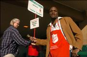 Laura Stull, Lawrence, drops in a donation while Salvation Army volunteer Arvelle Trotter, Lawrence, rings the bell Friday at Dillons, 3000 W. Sixth St. The Salvation Army will kick off its annual kettle fundraising campaign today.