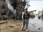 A U.S. soldier, right, secures the area where two car bombs detonated Friday in a central Baghdad, Iraq, residential neighborhood, killing at least six people and injuring 43 more between an Interior Ministry building and a hotel occupied by foreign journalists.