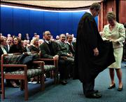 Judge Eric Rosen is helped by his wife, Libby, into his new robe Friday before being sworn in as a justice to the Kansas Supreme Court in Topeka.
