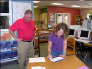 Sherry Emerson, of Pet World, signs an agreement Oct. 4 to become a Lawrence Education Achievement Partner with Broken Arrow School as the school's principal, Larry Bakerink, looks on. As a partner with Broken Arrow, employees will support the education of nature and animals in a variety of ways.
