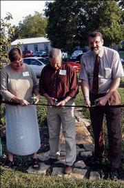 From left, Julie Coleman, of Kansas Department of Health and Environment; Charles Jones, Douglas County commissioner; and Daryl Buchholz, associate director for Extension and Applied Research at Kansas State University, participate in a ribbon-cutting ceremony for the rain garden at the Douglas County Extension office. The dedication was part of the Douglas County Extension Showcase on Sept. 22.