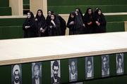 Female Iranian students walk past photos of dead lawmakers during the morning session of parliament Sunday in Tehran, Iran. Parliament approved a bill on Sunday that requires the government to block intrusive inspections of Iran's facilities if the U.N. nuclear agency refers the Iranian program to the U.N. Security Council.