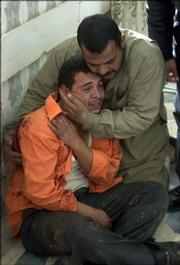 A man is consoled by a relative as he mourns the death of his family members Monday inside Baqouba hospital, Iraq. U.S. forces mistakenly fired on a civilian vehicle outside of an American military base north of Baghdad on Monday, killing at least three people, including one child, a U.S. spokesman said. Iraqi police said four people were killed. The reason for the discrepancy was unclear.