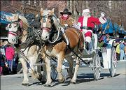 Santa Claus parades down Massachusetts Street in a horse-drawn carriage. This year's Old Fashioned Christmas Parade, in its 13th year, is shaping up to be the largest ever.
