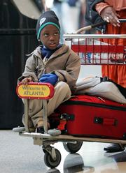 Demaine Williams, 5, rides on a luggage cart at Hartsfield Jackson Atlanta International Airport in Atlanta, as he and his family return home to Nassau, Bahamas, after visiting in Atlanta. Airport officials were expecting some 285,000 people to pass through Hartsfield Jackson on Tuesday, one of the busiest travel days leading up to Thanksgiving.