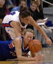 Kansas University's Kaylee Brown, top, dives for a loose ball against Detroit's Caitie Goddard in the first half of KU's 70-68 victory. Kansas won Tuesday in Allen Fieldhouse.