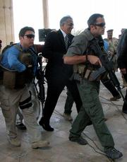 U.S. Ambassador to Iraq Zalmay Khalilzad, center, is escorted by armed guards Tuesday soon after insurgents fired a mortar at a U.S. ceremony, sending the U.S. ambassador scrambling for cover but causing no injuries in Tikrit, Iraq.