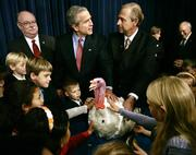 President Bush invites local schoolchildren to pet Marshmallow, the beneficiary of this Thanksgiving's traditional presidential pardon, Tuesday in Washington. Turkey farmer James Trites, right, steadies Marshmallow. National Turkey Federation Chairman Pete Rothfork watches at left.