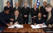 Secretary of State Condoleezza Rice, seated at right, and Bosnian Foreign Minister Mladen Ivanic, seated at left, sign a Status of Forces Agreement and an Open Skies Agreement at the State Department on Tuesday in Washington. In the back row are the Croat member of the Bosnian three-member presidency, Ivo Miro Jovic, center, Sulejman Tihic, second from left, the Bosnian Muslim member, and Borislav Paravac, the Serb member, second from right. Others are unidentified.