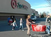 Shoppers leave SuperTarget along South Iowa Street on Wednesday. The discounters are across the street from each other in Lawrence, and their parent companies are changing strategies, adding products and adjusting marketing plans for this holiday season - working to line up maximum sales during what traditionally is a pivotal period for retailers nationwide.