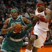 Boston's Paul Pierce, left, tries to drive past Atlanta's Josh Smith. Pierce scored 33 points, but the Celtics fell, 120-117, Wednesday night in Atlanta.