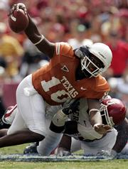 Texas quarterback Vince Young is tackled by Oklahoma's Nic Harris. The action took place Oct. 8 in Dallas. Young needs a big game Friday against Texas A&M to make his case for the Heisman Trophy.