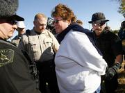 Dede Miller, sister of Cindy Sheehan, is arrested by McLennan County Sheriff's deputies Wednesday for camping in a county ditch in Crawford, Texas. A dozen war protesters, including a Lawrence woman, were arrested Wednesday on trespassing charges.