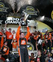 Tony Stewart, center, and team celebrate winning the 2005 NASCAR Nextel Cup Chase for the Championship.