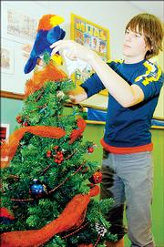 Scotty Thellman, a Central Junior High School student, helps decorate a Jayhawk-themed holiday tree for the Festival of Trees benefit. Central teacher Linda Hyler and her classes also created a K-State themed tree for the event, which raises funds for The Shelter Inc.