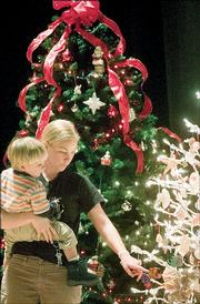 Liz prosser, Lawrence, and her son Thomas Prosser, 2, look at a decorated holiday tree on display at Liberty Hall as part of the 2004 Festival of Trees.