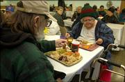 Patrick Eklund, left, and Lani Oglesby attend the annual Lawrence Interdenominational Nutrition Kitchen's Thanksgiving meal. They were among 178 people who enjoyed Thursday's dinner.