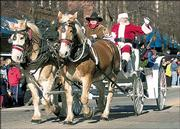 SANTA CLAUS greets spectators from a horse-drawn carriage during the 2004 Lawrence Old-Fashioned Christmas Parade. CornerBank assumed leadership of the parade last year and also will coordinate the 2005 event, which will be Dec. 3.
