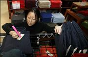 Kysha Kiive marks men's shirts down from $24.98 to $19.99 Wednesday at a Macy's store in downtown Seattle. Retailers across the country are gearing up for today, traditionally one of the biggest shopping days of the year.