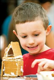 James Harader-Ellet, a Schwegler School student, constructs a gingerbread house to sell in the 2004 Gingerbread House Festival and Auction for Big Brothers/Big Sisters. Public viewing times for the festival, held at the Eldridge Hotel, 701 Mass., will begin Friday.