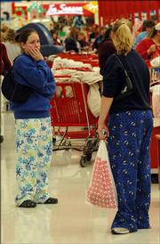 "Sara Hegeman, a Lawrence High School sophomore, left, and friend Mandy Zwiener, a Free State High School sophomore, shop at SuperTarget in their pajamas. ""We&squot;re exhausted,"" said Zwiener who, with Hegeman, was at Kohl&squot;s at 5 a.m. ""We&squot;ll be back in bed by 10 a.m."" Hegeman said."